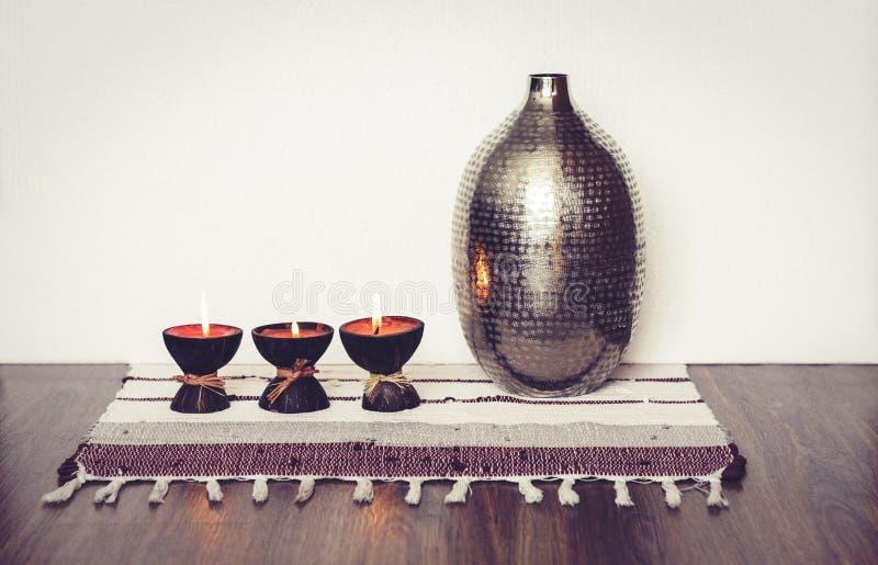 Decoración interior casera acogedora, velas ardientes en cáscara del coco en una manta multicolora con el fondo del florero del m foto de archivo