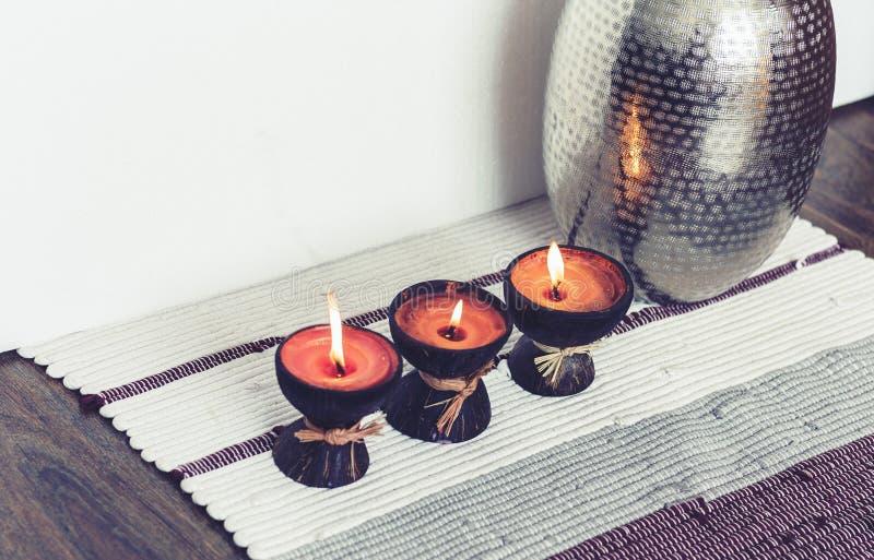 Decoración interior casera acogedora, velas ardientes en cáscara del coco en una manta multicolora con el fondo del florero del m imagen de archivo libre de regalías