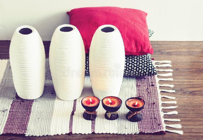 Decoración interior casera acogedora, velas ardientes en cáscara del coco en una manta multicolora con los floreros de cerámica b imagenes de archivo