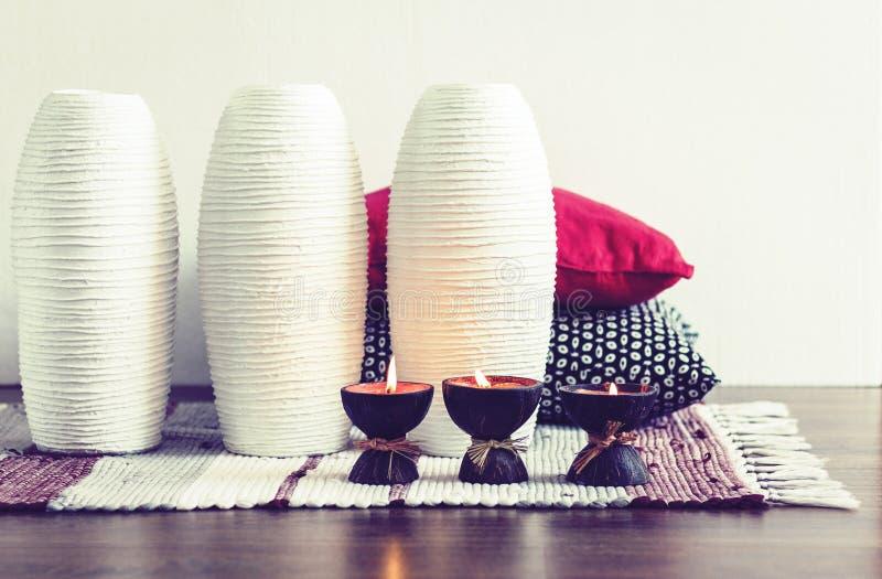 Decoración interior casera acogedora, velas ardientes en cáscara del coco en una manta multicolora con los floreros de cerámica b imágenes de archivo libres de regalías