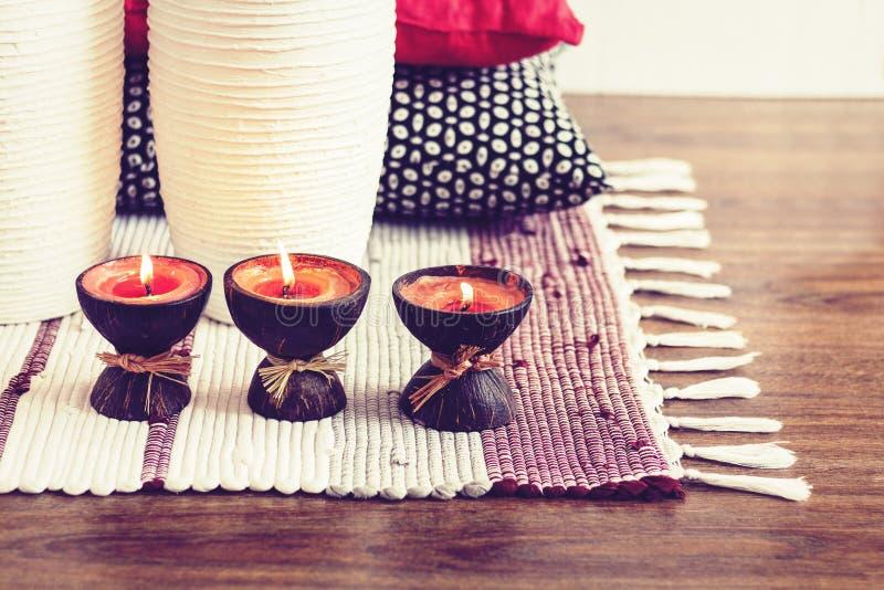 Decoración interior casera acogedora, velas ardientes en cáscara del coco en una manta multicolora con los floreros de cerámica b imagen de archivo