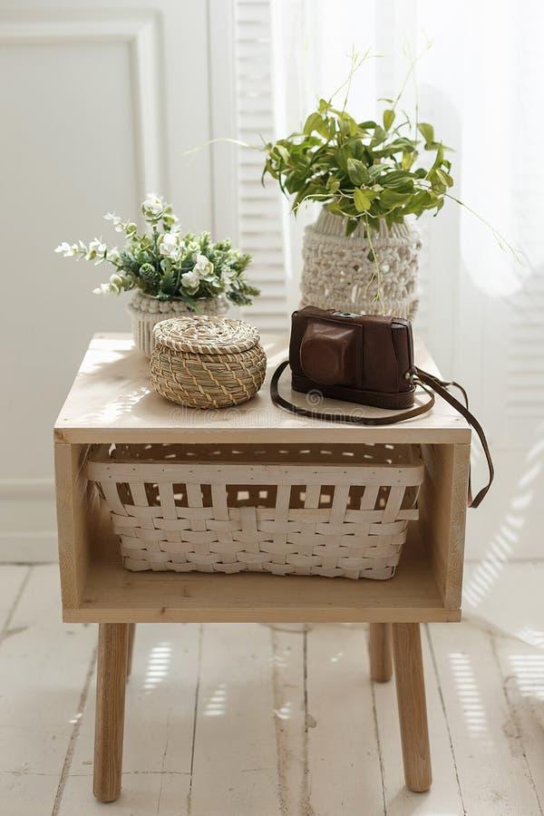 Decoración interior casera con los pequeños potes de la planta, cesta y caja verdes del photocamera en una tabla Concepto interio imágenes de archivo libres de regalías