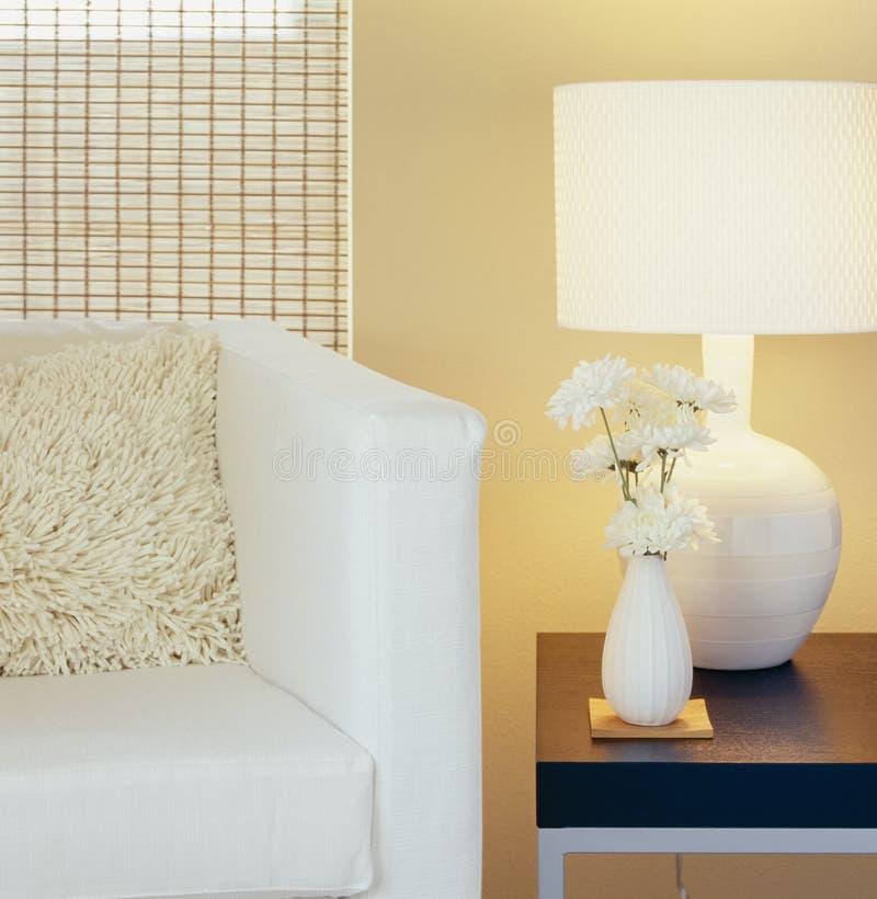 Decoración interior casera moderna Sala de estar con la silla, la almohada, la tabla, la lámpara, la pared pintada, las persianas imagenes de archivo