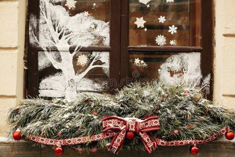 Decoración navideña. Estilosas ramas de abetos nevados con el arco rojo festivo y bolas en la tienda de ventanas en el mercado d foto de archivo libre de regalías