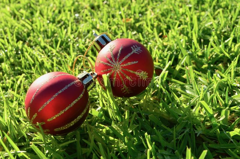 2 decoración que brilla roja y del oro de la Navidad de las bolas en la Navidad de la hierba en julio fotos de archivo