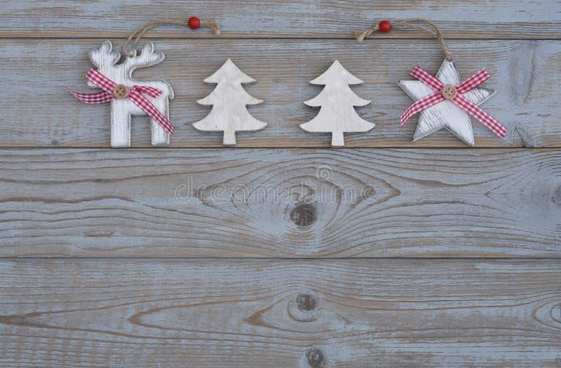 Decoración roja blanca de la Navidad como el árbol de navidad, el reno y estrella en un viejo fondo de madera gris de los tablone imagenes de archivo