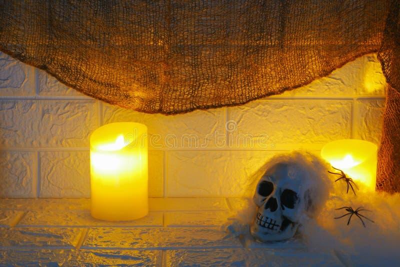 Decoración, velas y cráneo de Halloween en fondo de la pared imágenes de archivo libres de regalías