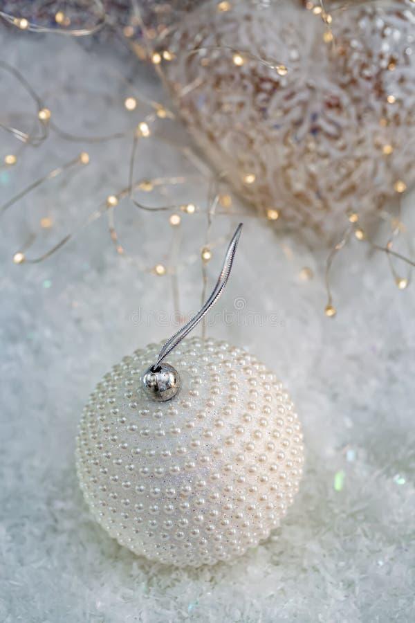 Decoraci?n de la Navidad Perlas blancas del n?car de la bola en una nieve y un fondo borroso hermoso del bokeh que brilla con las fotos de archivo