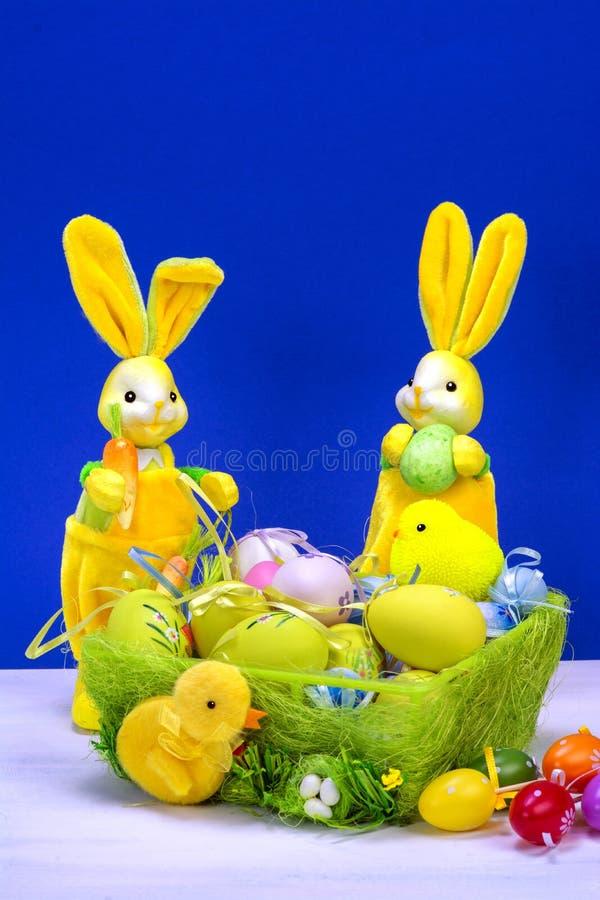 Decoraci?n de Pascua, conejito de pascua amarillo dulce, conejos con el pollo en cesta y los huevos de Pascua, en la tabla blanca imagen de archivo libre de regalías
