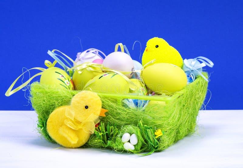 Decoraci?n de Pascua, conejito de pascua amarillo dulce, conejos con el pollo en cesta y los huevos de Pascua, en la tabla blanca fotografía de archivo