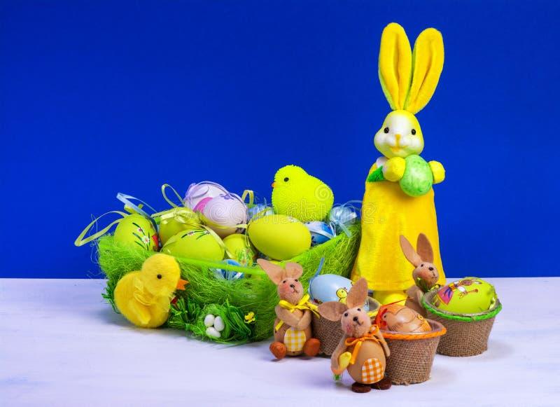 Decoraci?n de Pascua, conejito de pascua amarillo dulce, conejos con el pollo en cesta y los huevos de Pascua, en la tabla blanca foto de archivo