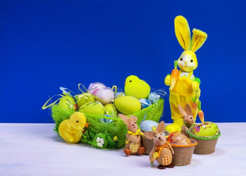 Decoraci?n de Pascua, conejito de pascua amarillo dulce, conejos con el pollo en cesta y los huevos de Pascua, en la tabla blanca fotos de archivo libres de regalías