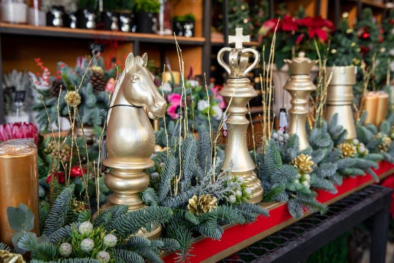 Decoraci?n del invierno. Bonito arreglo de piezas de ajedrez doradas, ramas de abeto natural, conos dorados para el lujo Navidad A imágenes de archivo libres de regalías