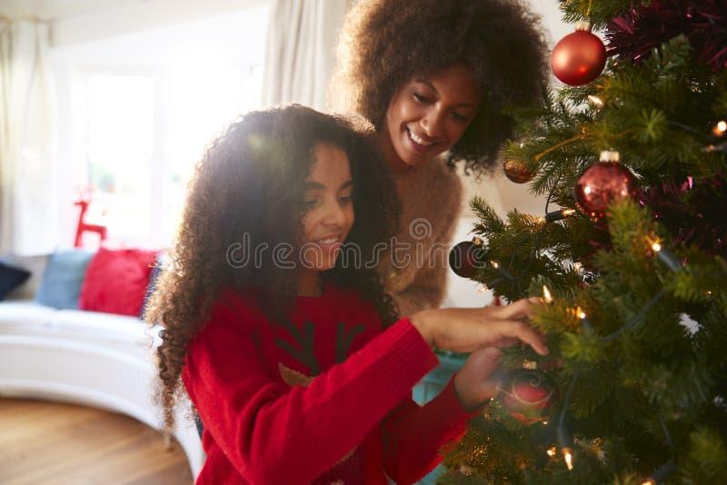 Decoraciones colgantes de la madre y de la hija en el árbol de navidad en casa fotografía de archivo