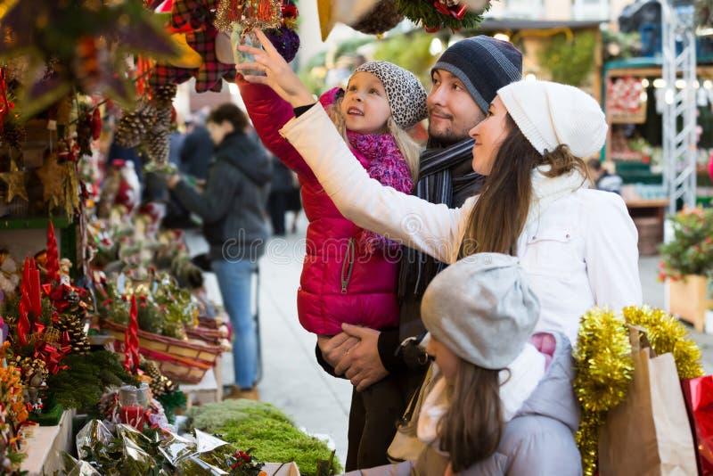 Decoraciones de compra de la familia en el mercado de la Navidad foto de archivo