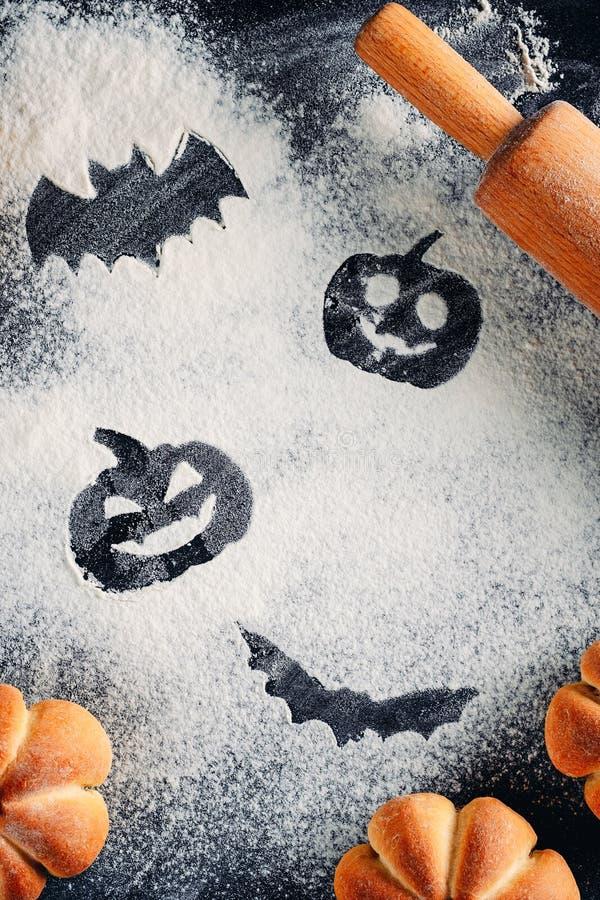 Decoraciones de Halloween del dibujo en fondo de la harina, tortas en la forma de la calabaza y rodillo Halloween que cocina conc imagen de archivo libre de regalías