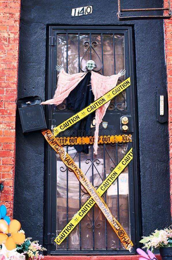 Decoraciones de Halloween incluyendo una bruja y rayas decorativas de la policía en la puerta principal de una casa en Brooklyn,  fotos de archivo