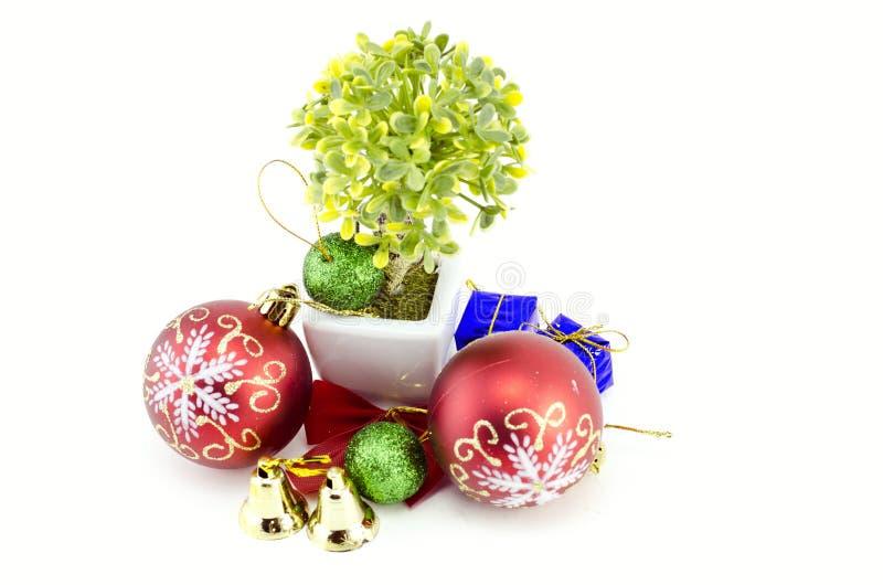Decoraciones de la Navidad con la bola roja, la bola verde, la cinta roja, la campana, el pequeño árbol en el pote blanco, y la f foto de archivo libre de regalías