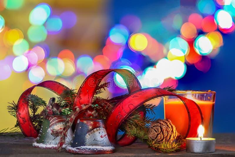 Decoraciones de la Navidad con las campanas, la cinta roja y las velas bajo fondo defocused imagenes de archivo