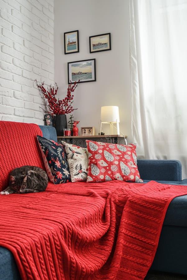 Decoraciones de la Navidad con las velas y tela escocesa roja en el sofá fotos de archivo libres de regalías