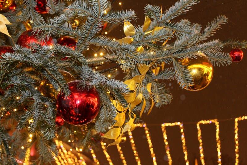 Decoraciones de la Navidad en el árbol de navidad en rojo y colores oro derramado con las luces, primer imagenes de archivo