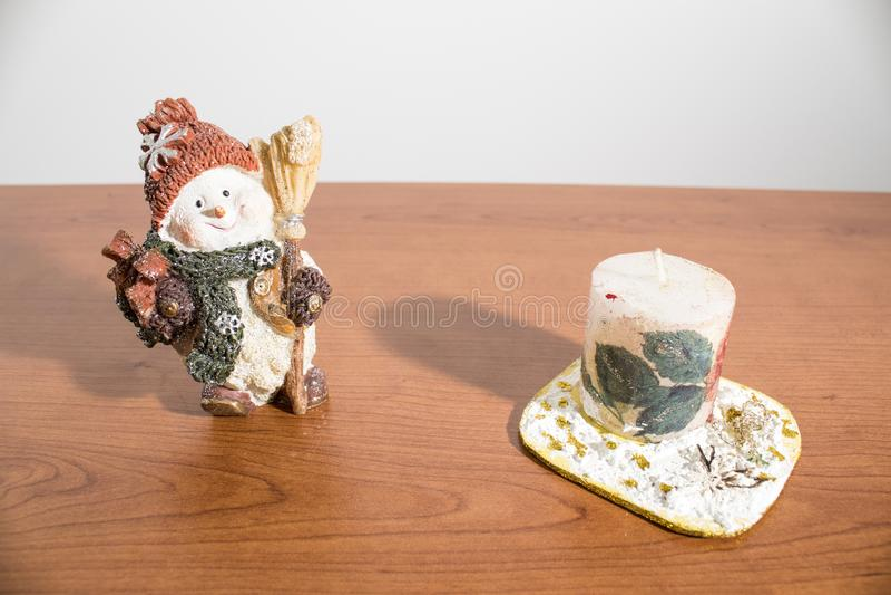 Decoraciones de la Navidad, muñeco de nieve y una vela en una tabla de madera imágenes de archivo libres de regalías