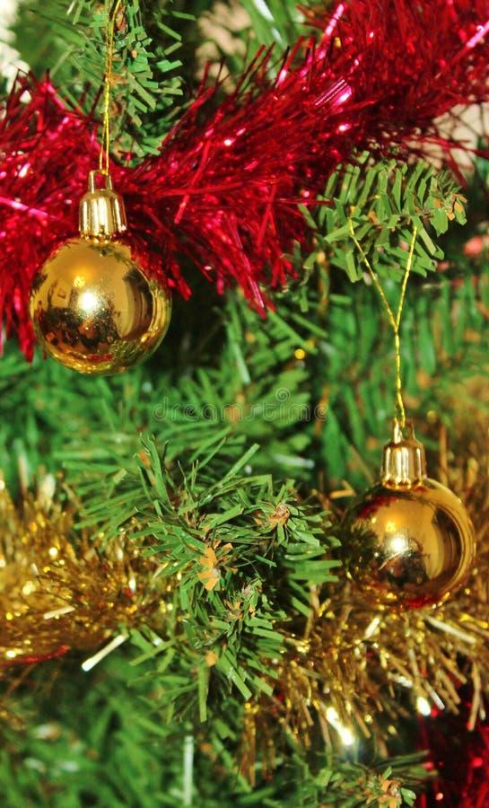 Decoraciones de la Navidad para el árbol en brillo y rojo del oro fotos de archivo