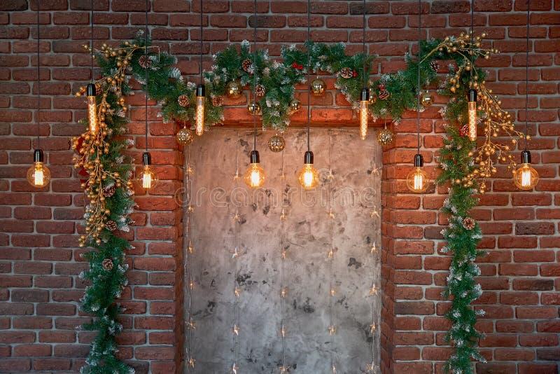 Decoraciones de la Navidad sobre la chimenea decorativa en la pared imagenes de archivo