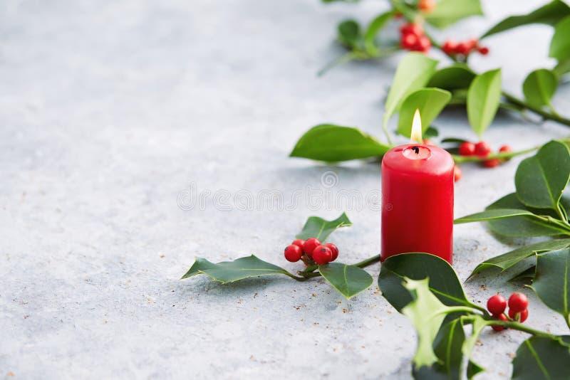 Decoraciones de la Navidad, vela y hojas del acebo con las bayas rojas imágenes de archivo libres de regalías