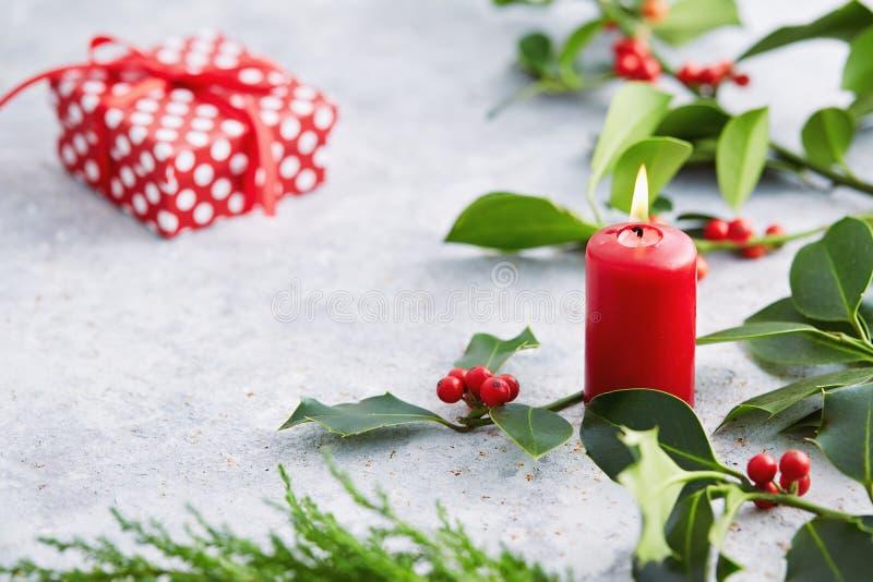 Decoraciones de la Navidad, vela y hojas del acebo con las bayas rojas imagenes de archivo