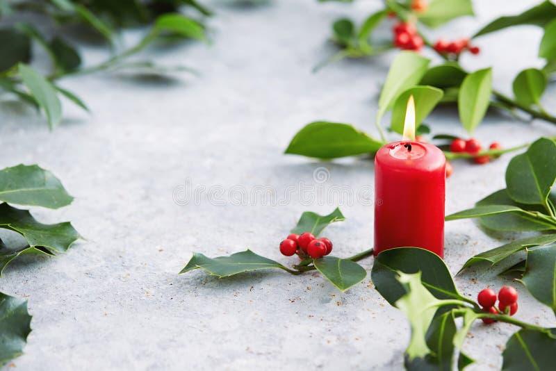 Decoraciones de la Navidad, vela y hojas del acebo con las bayas rojas fotos de archivo libres de regalías