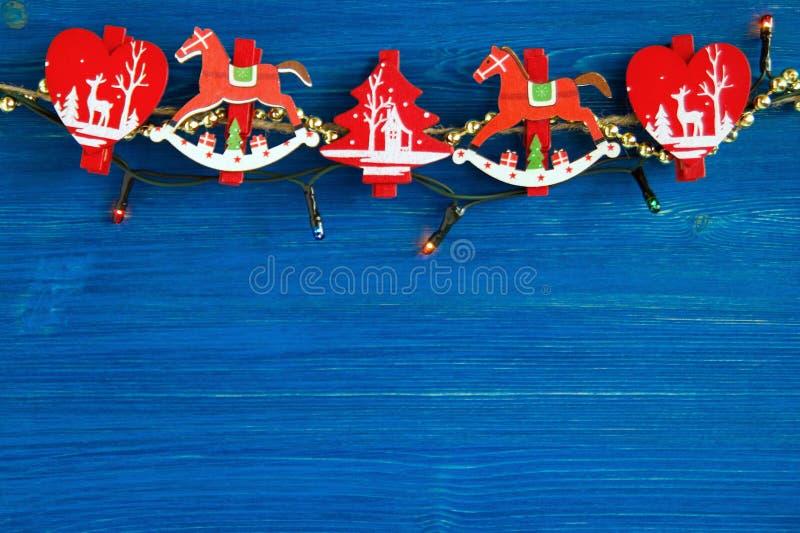 Decoraciones de la Navidad y luces de la Navidad de madera rojas y blancas en el fondo de madera azul fotografía de archivo libre de regalías