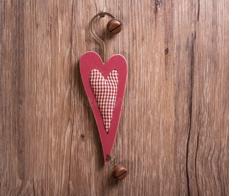 Decoraciones de madera corazón de la Navidad y ejecución de la campana de la Navidad encendido imagen de archivo