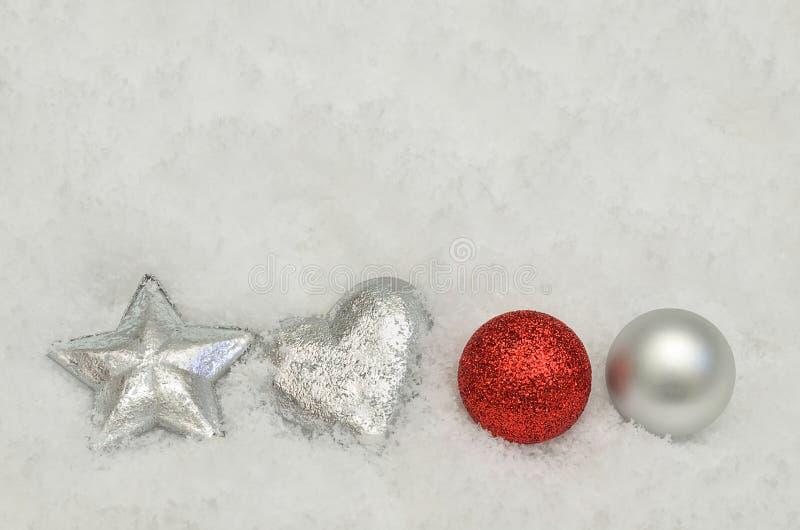 Decoraciones de plata y rojas del árbol de navidad en fondo de la nieve foto de archivo