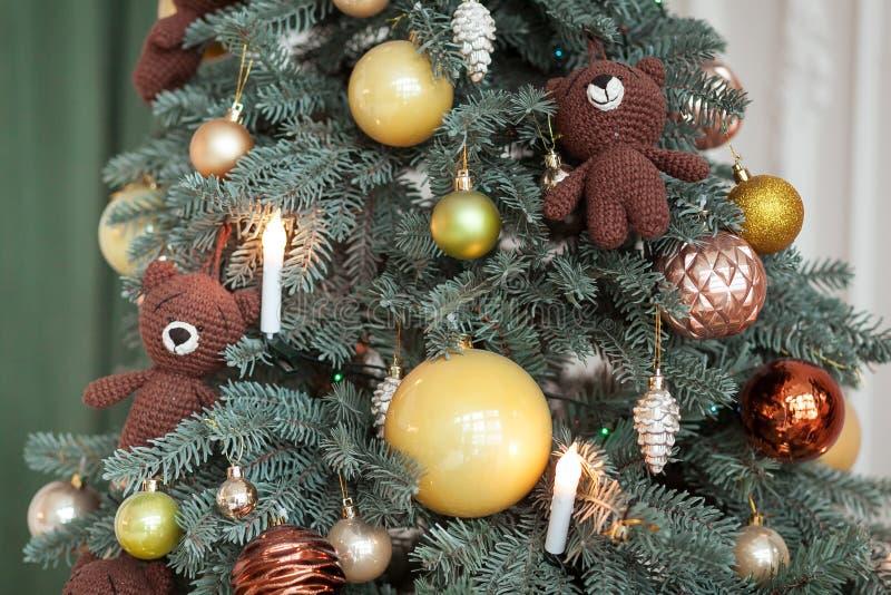 Decoraciones del árbol de navidad El juguete hizo punto el oso, luces de la guirnalda y bolas del vintage en picea Ciérrese encim imagen de archivo libre de regalías