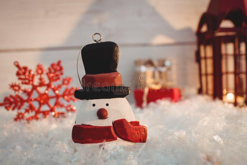 Decoraciones del muñeco de nieve y de la Navidad en nieve falsa fotografía de archivo