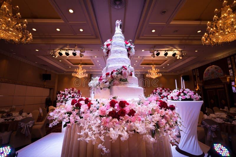Decoraciones del pastel de bodas y de las flores con la lámpara en techo imagen de archivo libre de regalías