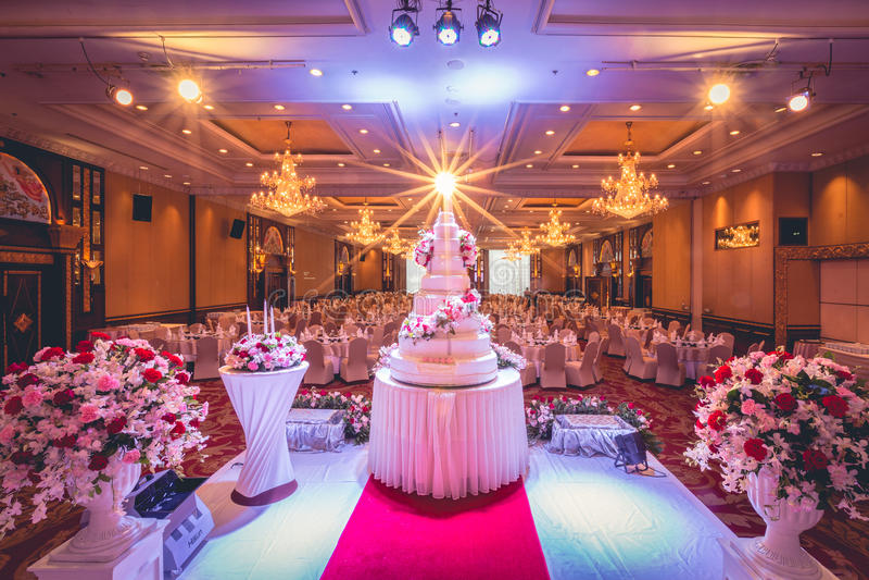 Decoraciones del pastel de bodas y de las flores con la lámpara en techo foto de archivo libre de regalías