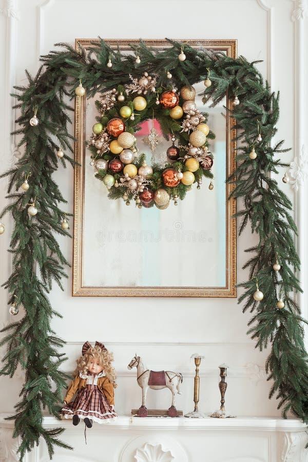 Decoraciones en la chimenea de la Navidad bajo la forma de palmatorias, guirnalda y marco de la foto, muñeca de la Navidad del vi fotos de archivo