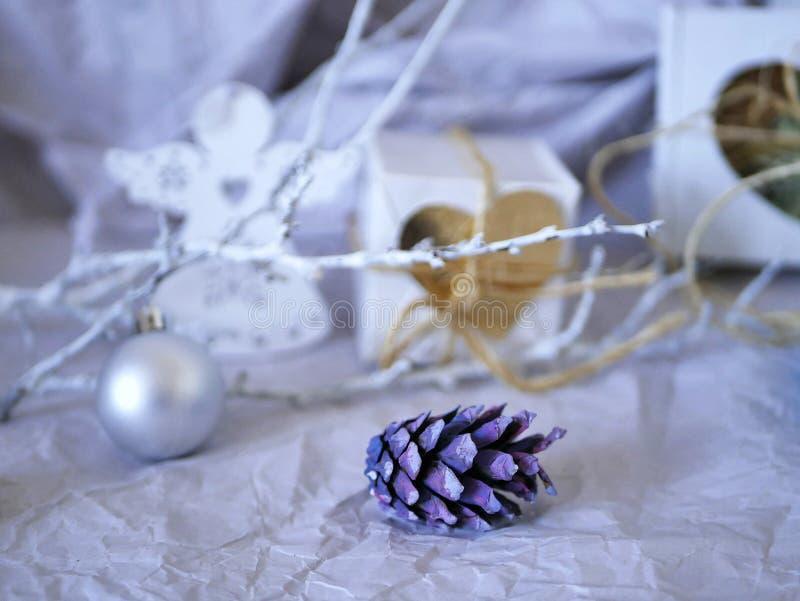 Decoraciones festivas de la Navidad de los conos púrpuras, ramas blancas, bola de plata, regalos en un fondo ligero fotos de archivo libres de regalías