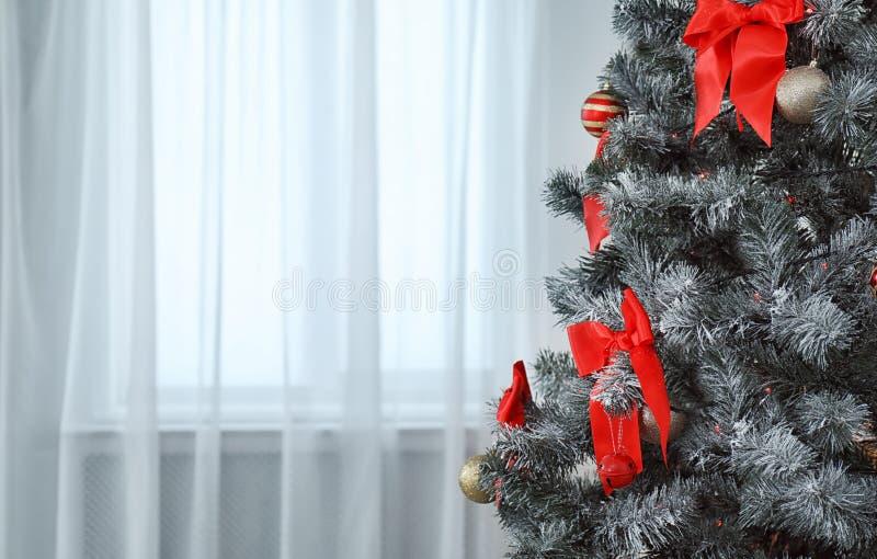 Decoraciones festivas en el árbol de navidad en interior vivo elegante imagenes de archivo