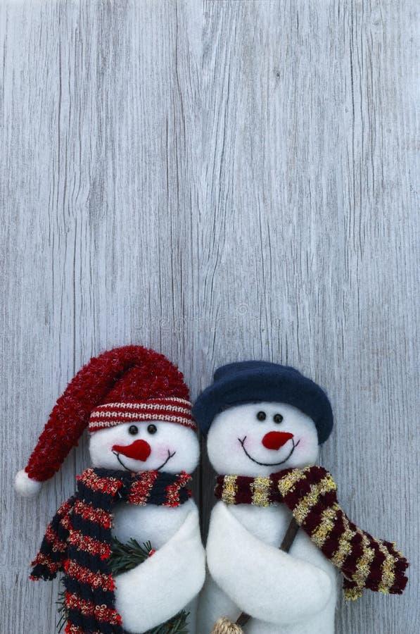 Decoraciones inmóviles de los muñecos de nieve de la vida de la Navidad en el fondo de madera blanco del tablón imagen de archivo