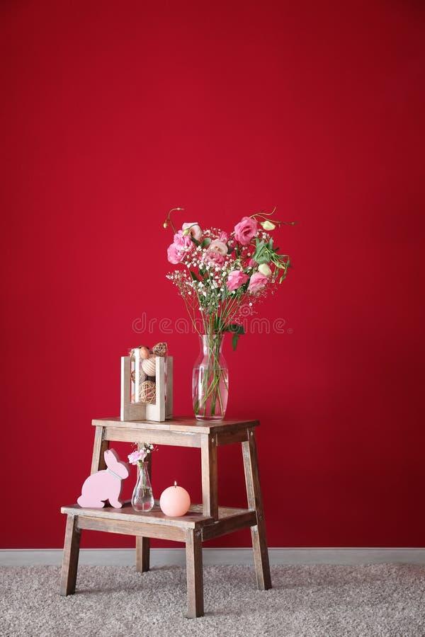 Decoraciones interiores y florero con las flores rosadas hermosas en soporte de madera cerca de la pared del color fotos de archivo