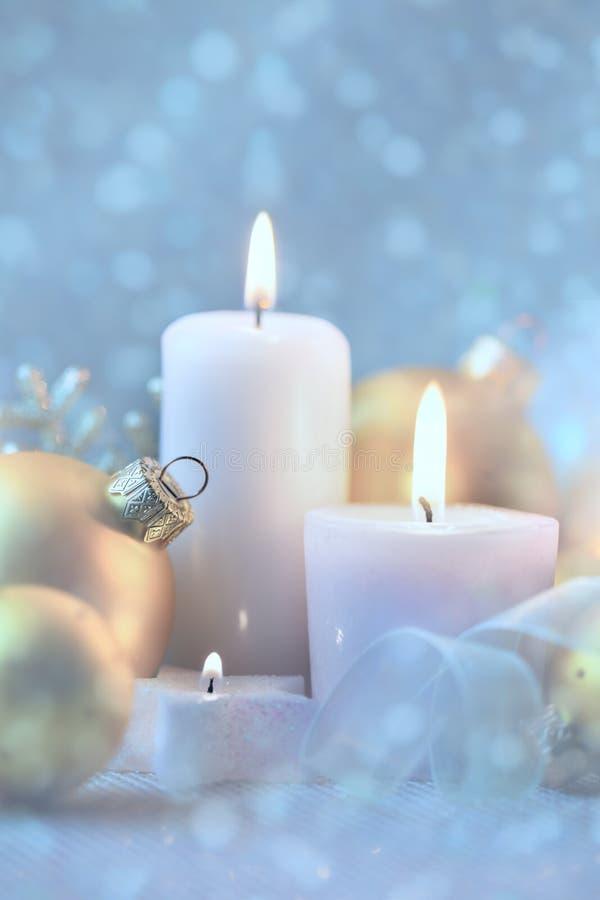 Decoraciones ligeras de la Navidad con las velas, las chucherías y la nieve mágica foto de archivo