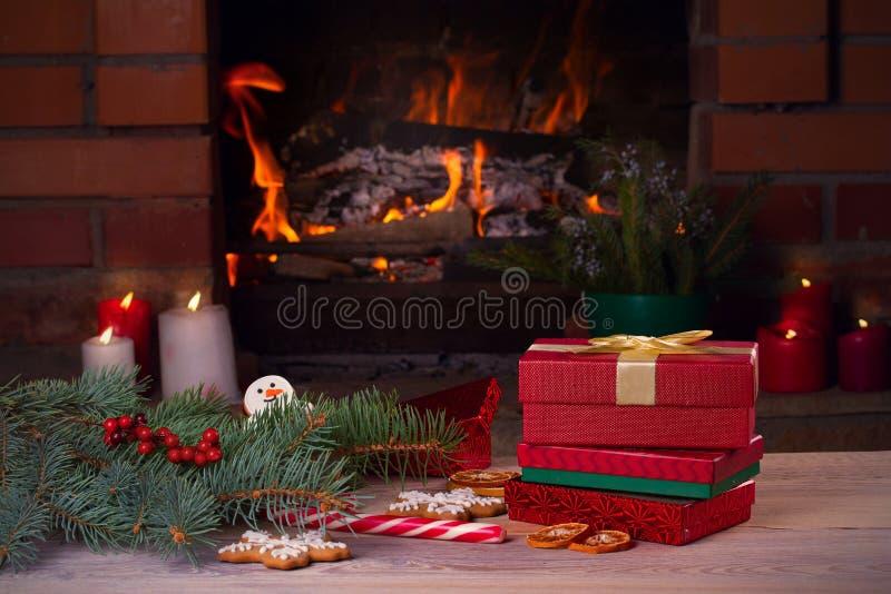 Decoraciones, regalos y galletas de la Navidad en la tabla de madera al lado del lugar abierto acogedor del fuego imágenes de archivo libres de regalías