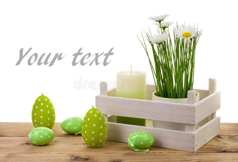Decoraciones vela, huevos y flor de Pascua en pote en el fondo de madera imagenes de archivo
