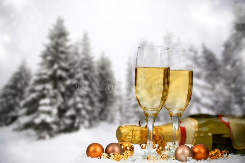 Decoraciones y champán de la Navidad contra fondo del invierno foto de archivo