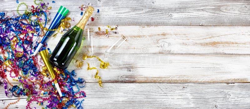 Decoraciones y champán del partido del Año Nuevo en la madera blanca rústica imagenes de archivo