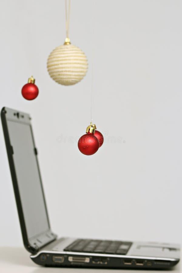 Decoraciones y ordenador portátil coloridos de las bolas de la Navidad imagenes de archivo