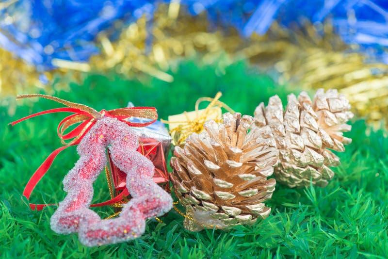 Decoraciones y ornamentos de la Navidad en fondo de la hierba verde imagenes de archivo